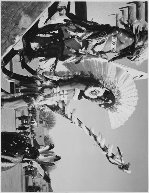 "Ansel Adams: Three Tewa men in headdress in foreground watching tourists, ""Dance, San Ildefonso Pueblo, New Mexico, 1942"
