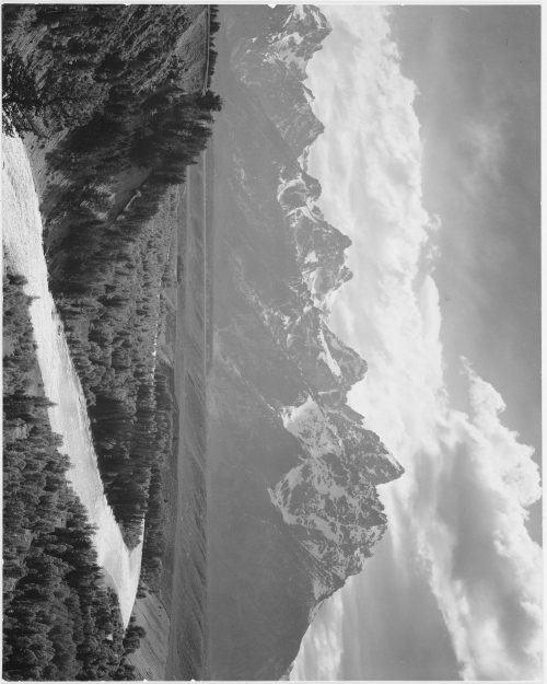 "Ansel Adams: View from river valley towards snow covered mountains, river in foreground from left to right, ""Grand Teton"" National Park, Wyoming"